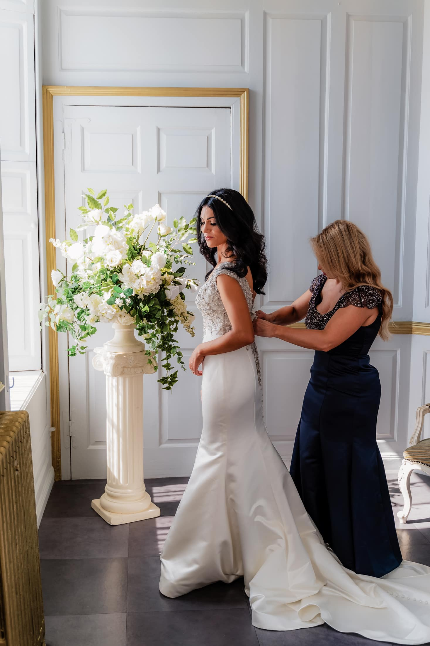 Bride in the rococo bridal suite getting her dress fitted -  essex summer wedding at gosfield hall