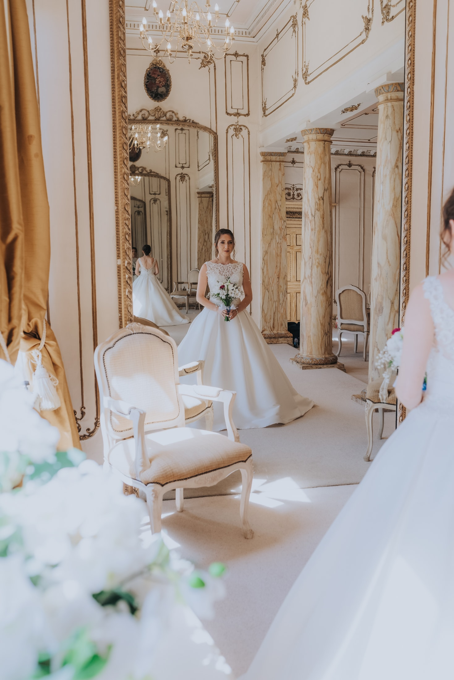 bride looking at herself in the mirrors in the gosfield hall bridal suite - rococo room