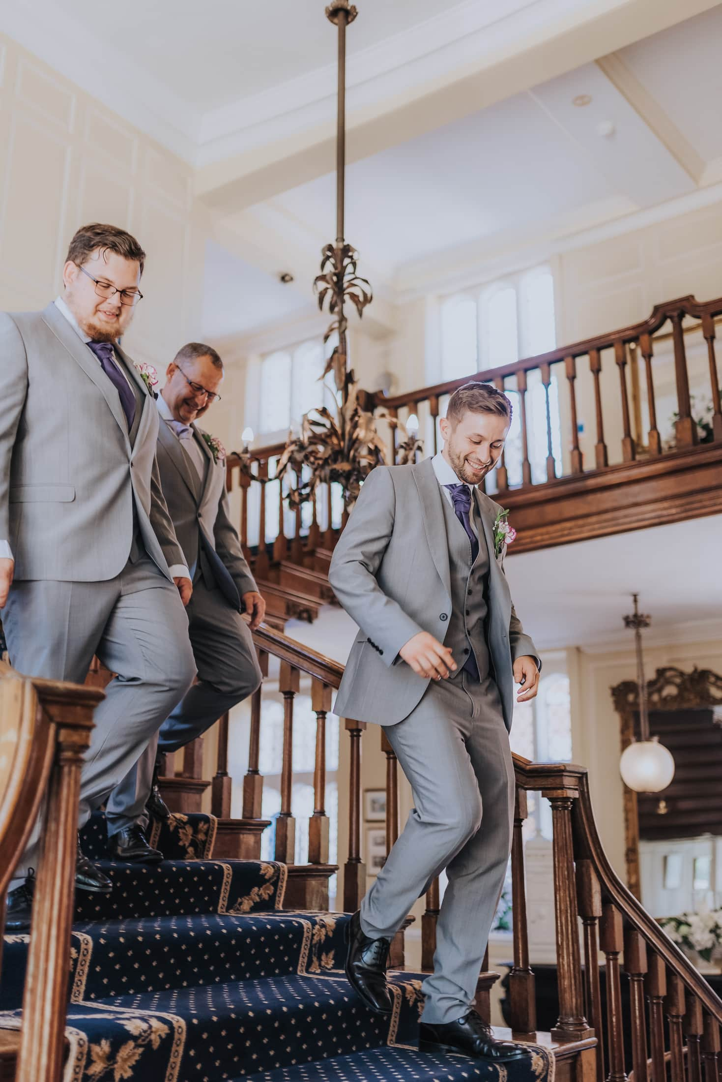 groomsmen walking down the main stairs at gosfield hall