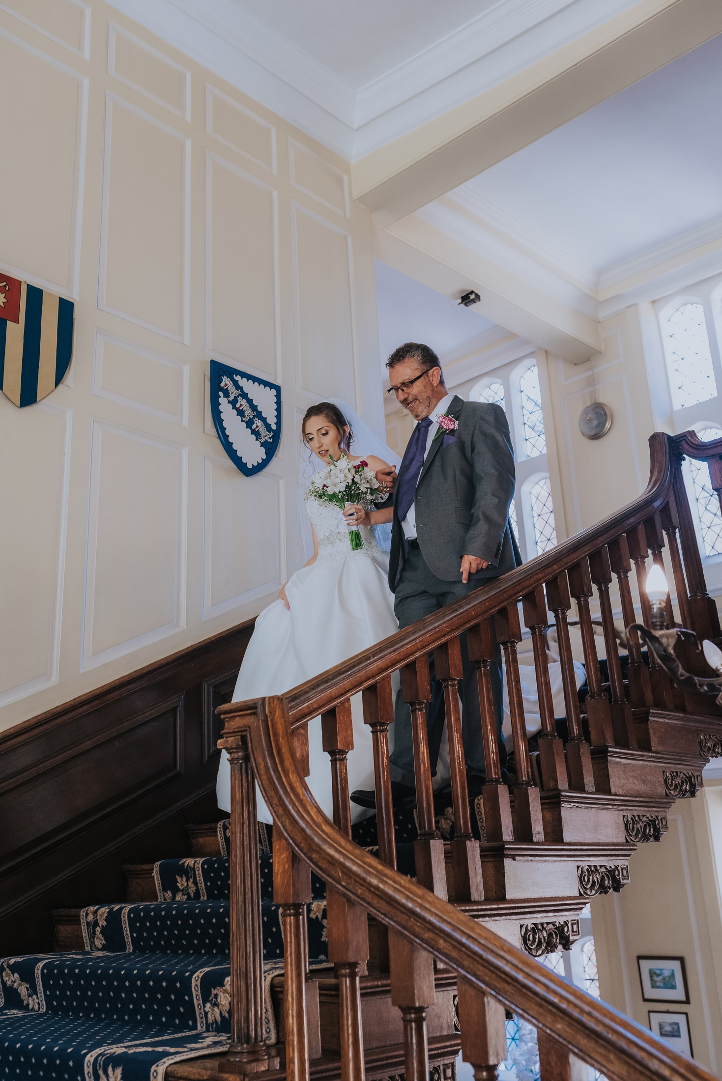 bride and her father walking down the stairs at gosfield hall wedding venue