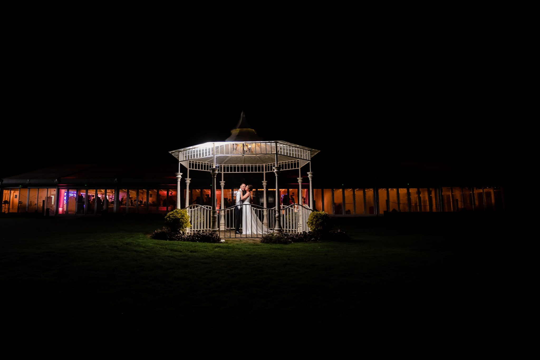 bride and groom under a pagoda at parklands quendon hall wedding venue - wedding photographer in Essex - lily and white