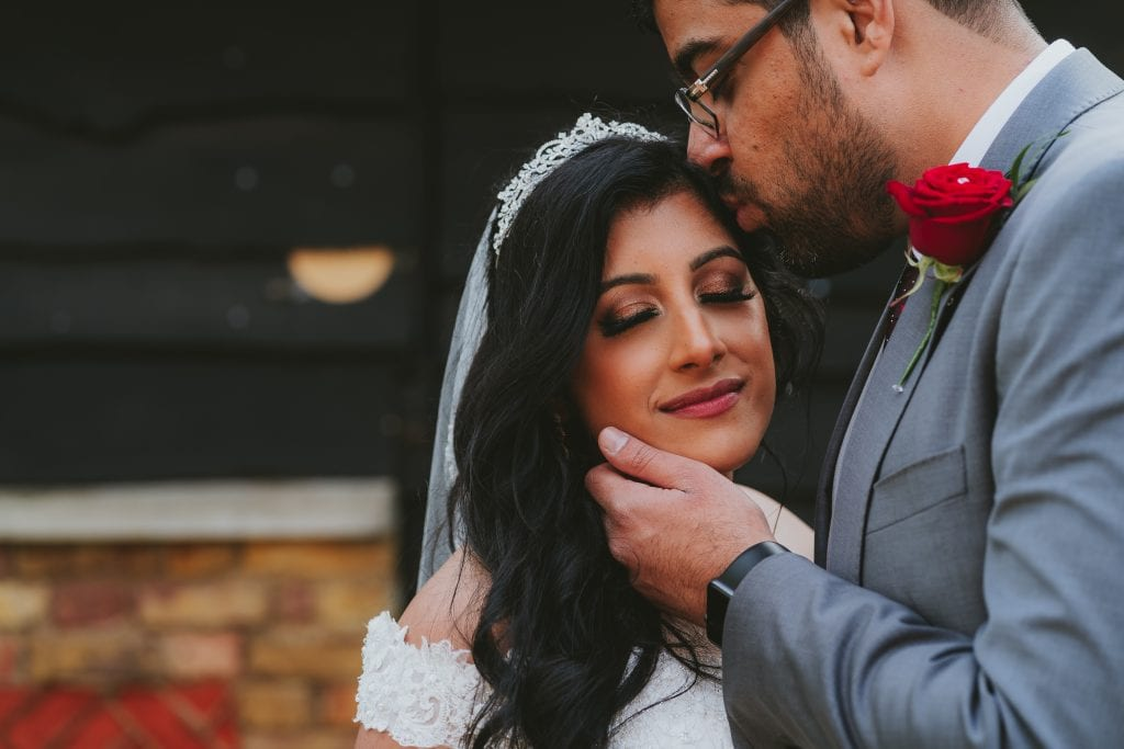 Bride and groom sharing a tender moment together at their Essex Wedding
