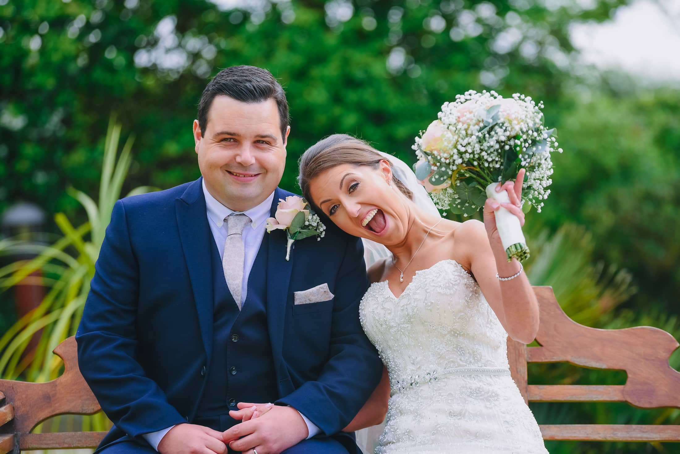 Bride and groom looking happy on the bench at friern manor wedding venue in essex